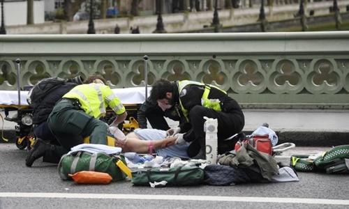 Một người bị thương được sơ cứu trong vụ tấn công ngoài tòa nhà quốc hội Anh hôm 22/3. Ảnh: Reuters
