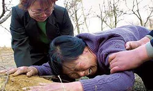 Mẹ của Nhiếp Thụ Bân đau khổ khóc bên mộ con trai sau khi Trung Quốc xác định đây là vụ án oan. Ảnh: SCMP