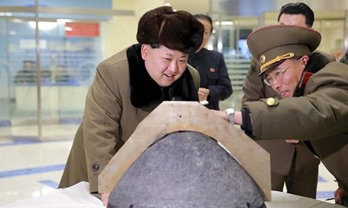 Nhà lãnh đạo Kim Jong-un xem một mô hình đầu đạn tên lửa. Ảnh: Reuters
