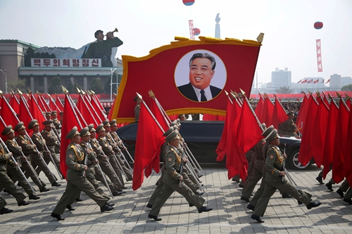 North Korean soldiers march past with a float carrying a picture of former supreme leader Kim Il-sung. HOW HWEE YOUNG / EPA