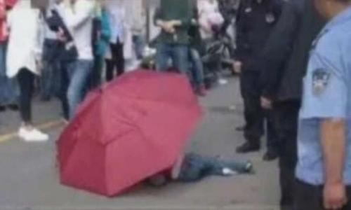 Bé trai Trung Quốc dùng ô nhảy từ nhà cao tầng xuống đất. Ảnh: Sohu