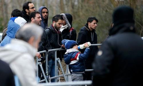 Người di cư đứng trước khu vực Văn phòng Liên bang Di cư và Tị nạn Đức. Ảnh: Reuters