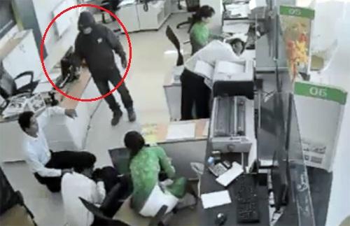 Tên cướp liên tục nạt nộ, dọa bắn các nhân viên, yêu cầu gom tiền bỏ vào 2 túi xách. Ảnh: Cắt từ video.