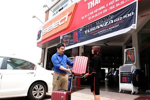 Khách hàng nhận vali từ đại lý khi mua hai lốp Bridgestone Turanza GR100.