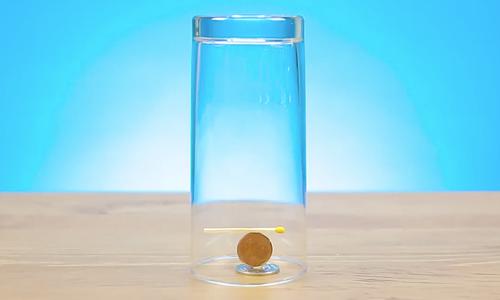 Một cái cốc, một que diêm, 2 đồng xu được sắp sếp như sau.