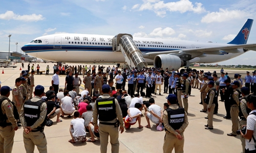 Chinese nationals suspected of telecom fraud are surrounded by Chinese police officials and Cambodia police before being deported to China, at the International Airport of Phnom Penh, Cambodia July 6, 2017