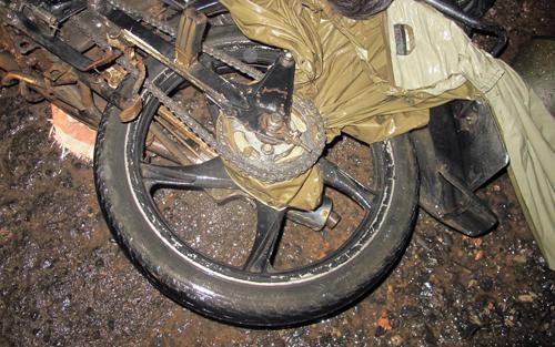 Áo mưa bị cuốn vào xích xe máy, siết cổ nạn nhân tử vong. Ảnh: Khánh Hương