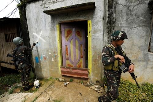 Binh sĩ Philippines đánh dấu một ngôi nhà đã được xác định là an toàn ở Marawi. Ảnh: Reuters.