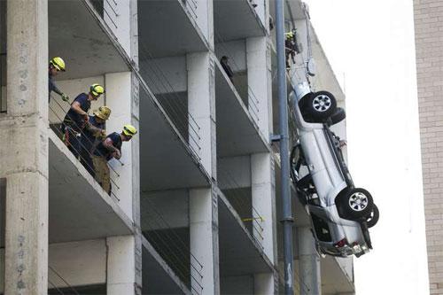 Chiếc SUV lao ra khỏi chỗ đỗ xe trên tầng cao và may mắn được một sợi dây rào giữ lại. Ảnh: ecommerce-journal