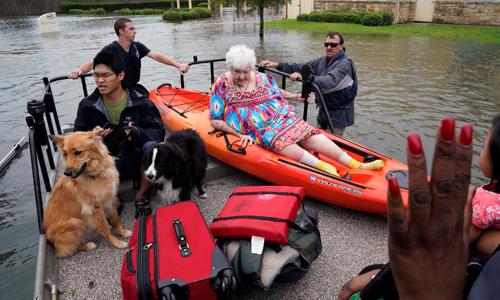 Người dân và vật nuôi ở Dickinson được đưa lên thuyền cứu hộ ngày 27/8. Ảnh: Reuters.