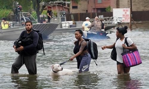 Người dân di chuyển qua một khu vực bị lụt ở thành phố Dickinson, Texas, ngày 27/8. Ảnh: Reuters.