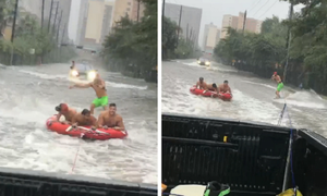 Ôtô kéo người chơi lướt ván trên đường mưa ngập