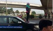 Người phụ nữ đứng trên nắp capo xe thanh tra phản đối dẹp vỉa hè