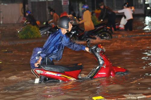 Quốc lộ 51 ngập nặng, nhiều xe chết máy phải dắt bộ qua đoạn đường ngập. Ảnh: Phước Tuấn