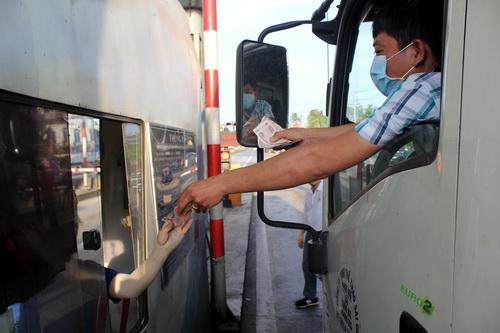 Khoảng 16h50, nhiều tài xế xe tải khi qua trạm BOT đường tránh sử dụng tiền lẻ. Ảnh: Phước Tuấn