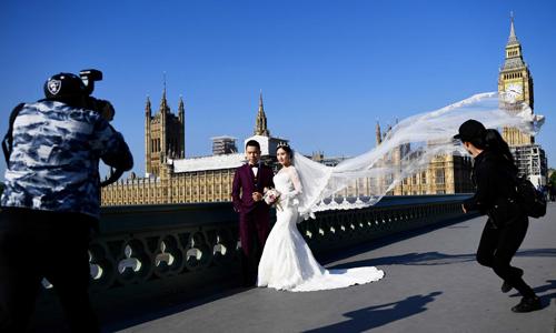 Cô dâu Jiachun Lin và chú rể Da Song tạo dáng trong buổi chụp hình ở cầu Westminster, London ngày 2/9. Ảnh: Reuters.