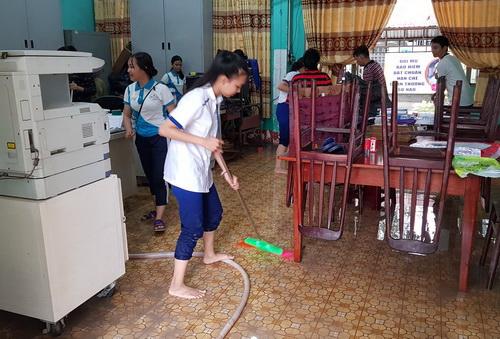 Thầy trò trường THPT Nguyễn Hữu Cảnh dọn dẹp phòng chức năng sau đợt ngập nặng rạng sáng nay. Ảnh: Phước Tuấ