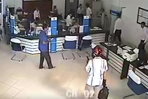 Tên cướp cầm súng khống chế mọi người trong ngân hàng. Ảnh: Cắt từ video.