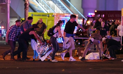 LAS VEGAS, NV - OCTOBER 02: An injured person is tended to in the intersection of Tropicana Ave. and Las Vegas Boulevard after a mass shooting at a country music festival nearby on October 2, 2017 in Las Vegas, Nevada. A gunman has opened fire on a music festival in Las Vegas, killing over 20 people. Police have confirmed that one suspect has been shot dead. The investigation is ongoing. Ethan Miller/Getty Images/AFP