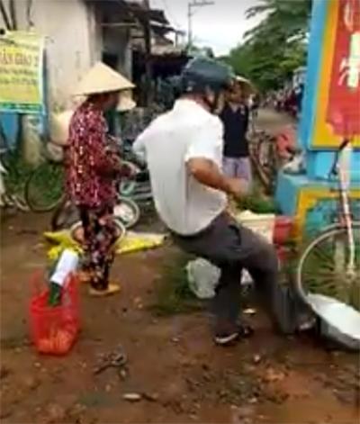 Trưởng công an xã đá văng nhiều thau đựng hàng hóa của người dân chiếm lòng đường. Ảnh: Cắt từ video.