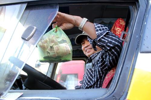 Nhiều tài xế ôtô đưa đón công nhân chuẩn bị tiền lẻ mua vé qua trạm BOT tuyến tránh Biên Hòa sáng nay. Ảnh: Phước Tuấn