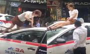 Cô gái ngáo đá chặn đầu taxi, trèo lên ngồi nóc xe