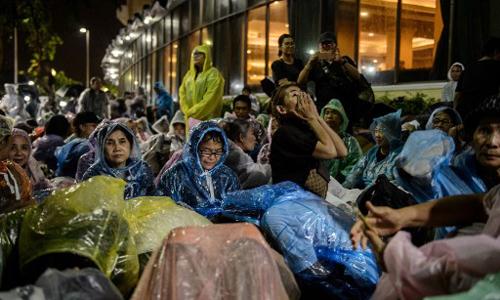 Người dân Thái Lan mặc áo mưa tối 24/10 ở Bangkok đợi tham dự lễ tang hoàng gia. Ảnh: AFP.
