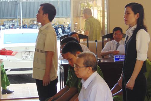 Nguyên giám đốc ngân hàng Quách Lạc (ngồi, áo trằng) hầu tòa cùng hai đồng phạm. Ảnh: Phúc Hưng.