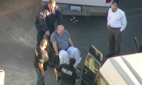 Bruce Paddock bị cảnh sát áp giải ra xe. Ảnh: KTLA.