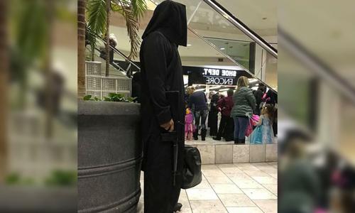 Người đàn ông Mỹ mặc trang phục đen có mũ trùm đầu, hai tay cầm túi và súng trường giả. Ảnh: Twitter.