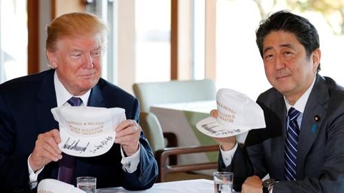 Tổng thống Mỹ Donald Trump và Thủ tướng Nhật Bản Shinzo Abe cầm mũ có dòng chữ