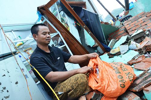 Anh Hùng nhặt kính vỡ sau trận bão bỏ vào bao tải. Ảnh: Phạm Linh.