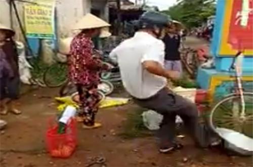 Trưởng công an xã đá thau cá của người buôn bán chiếm lòng lề đường. Ảnh: Cắt từ video.