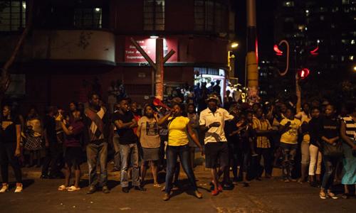 Người dân Zimbabwe ăn mừng trên phố ở quận Hillow, thành phố Johannesburg, Nam Phi tối 21/11. Ảnh: AFP.