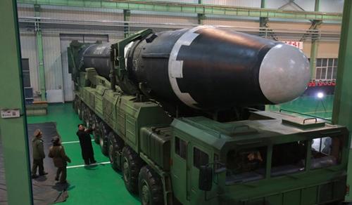 Lãnh đạo Triều Tiên đứng cạnh xe chở tên lửa Hwasong-15. Ảnh: KCNA.