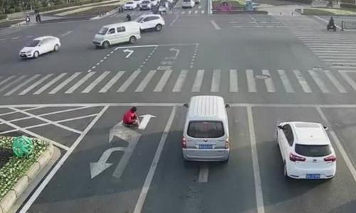 Người đàn ông Trung Quốc vẽ lại sơn tín hiệu giao thông. Ảnh: SCMP.