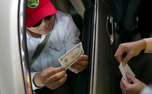 Một tài xế đưa tiền lẻ và được thối 100 đồng. Ảnh: Nguyễn Thành.