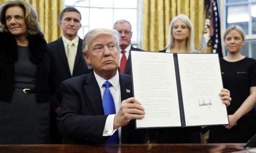Tổng thống Donald Trump ký một sắc lệnh tại Nhà Trắng hồi tháng 1. Ảnh: AP.
