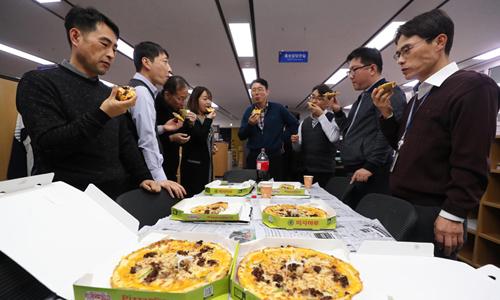 Cán bộ Bộ Chiến lược và Tài chính Hàn Quốc thưởng thức pizza do Tổng thống Moon Jae-in tặng. Ảnh: Yonhap.
