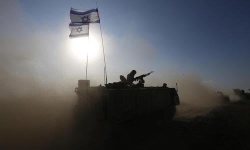 Binh sĩ Israel trên xe bọc thép chở quân tiến về khu vực biên giới với Gaza. Ảnh: Reuters.