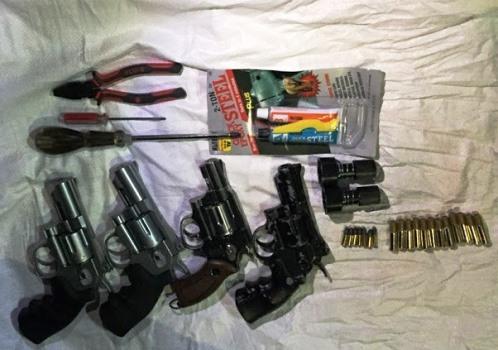 Khám xét nơi ở của nghi can, cảnh sát thu giữ nhiều khẩu súng ngắn. Ảnh: Nguyệt Triều.