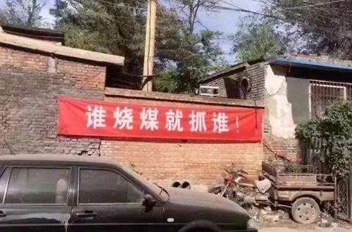 Băng rôn có dòng chữ Bất cứ ai đốt than cũng sẽ bị phát giác tại một ngôi làng ở Trung Quốc. Ảnh: CMN.
