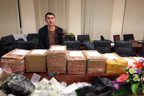 Thành cùng số tang vật hơn 600 chiếc điện thoại đựng trong tám thùng bìa carton. Ảnh: Cảnh sát cung cấp