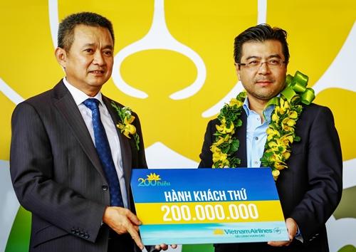 Hành khách thứ 200 triệu Nguyễn Trường Chinh (phải) nhận hoa chúc mừng từ Tổng giám đốc Vietnam Airlines Dương Trí Thành (trái). Ảnh: Thành Nguyễn