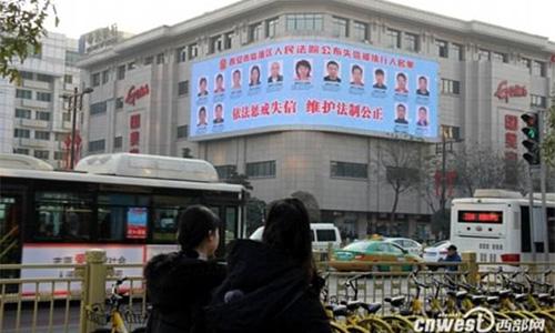 Tấm pano quảng cáo treo tại một ngã tư đông đúc ở thành phố Tây An in hình ảnh của những cá nhân nợ nần. Ảnh:Peoples Daily.