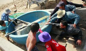 Ngư dân hối hả kéo thuyền lên bờ tránh bão Tembin