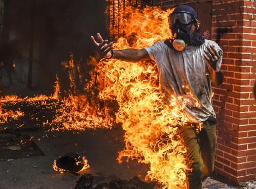 Một người biểu tình trở thành đuốc sống khi quần áo của anh ta bắt lửa khi cuộc biểu tình chống Tổng thống Venezuela Nicolás Maduro biến thành bạo loạn và đụng độ với cảnh sát ngày 3-5 - Ảnh: AFP