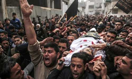 Mourners carry the body of 19-year-old Mohamed Sami al-Dahdouh, a Palestinian youth from Jabalia who was killed in clashes with Israeli forces east of Gaza City, during his funeral in Gaza City on December 24, 2017.