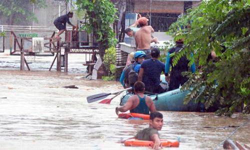 Lực lượng cứu hộ giúp người dân di tản khỏi nhà trong lũ lớn ở thành phố Cagayan de Oro. Ảnh: Reuters.