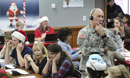 Tướng Charles D. Luckey tham gia đội tình nguyện trả lời điện thoại của trẻ em khắp thế giới trong hoạt động theo dõi đường đi của ông già Noel tại NORAD ở căn cứ không quân Peterson, Colorado ngày 24/12. Ảnh: AP.